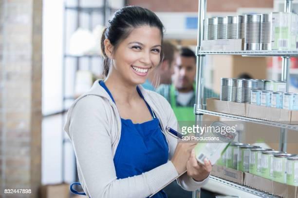 Weibliche Lebensmittelbank ehrenamtlich Bestände Regale