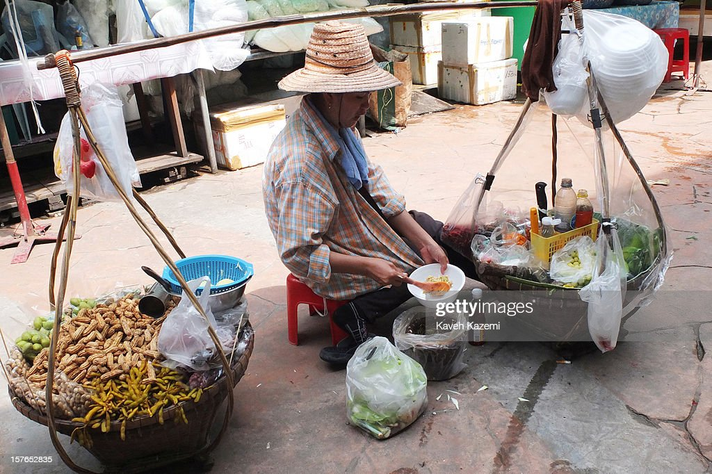 A female food vendor with a traditional carry on rack prepares a bowl of food on the street on October 25, 2012 in Bangkok, Thailand.