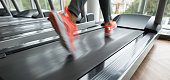 Female foot running on treadmill - motion blur