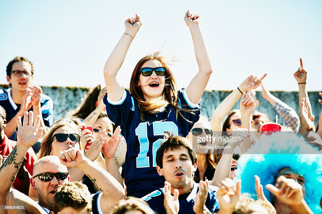 Female football fan standing in stadium cheering : Stock Photo