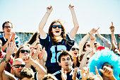 Female football fan standing in stadium cheering