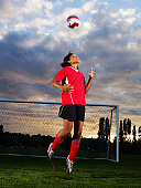 Female football player (10-11) jumping and heading ball in pitch