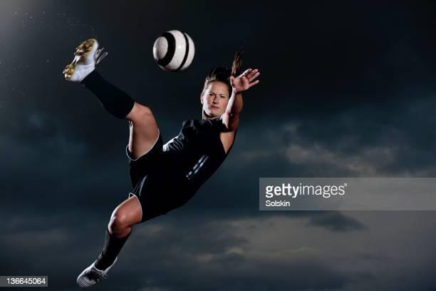 female football player kicking ball in mid air
