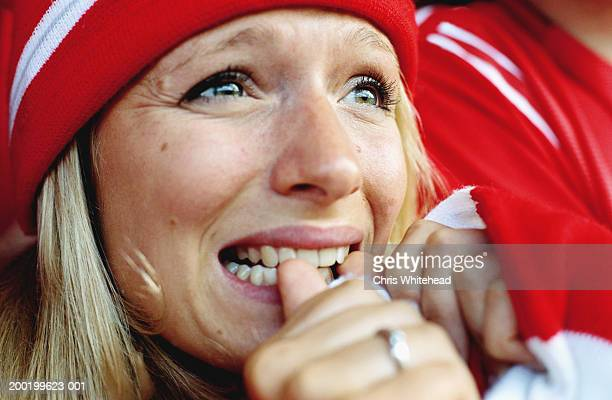 Female football supporter at match, biting nails, close-up