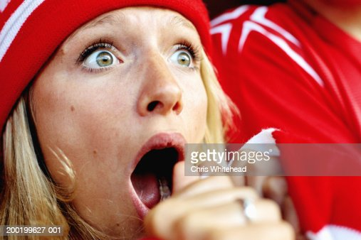 Female football supporter at match, gasping, close-up