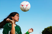 Female footballer (11-13) heading ball, low angle view