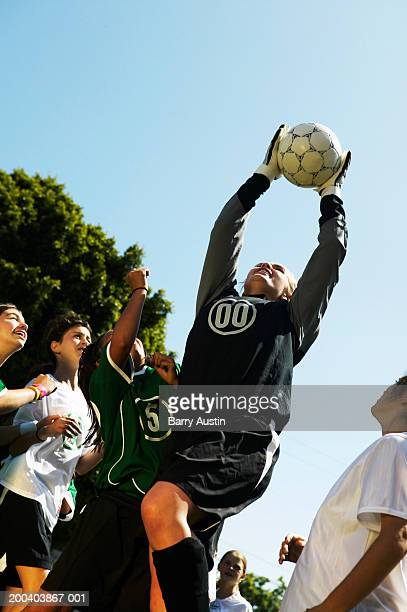 Female footballer (11-13) jumping for ball, low angle view