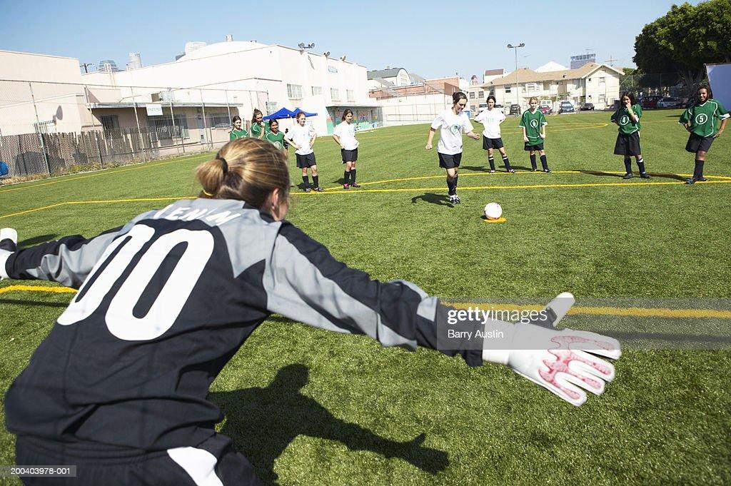 Female footballer (12-14) taking penalty, rear view of goalie : Stock Photo