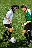 Female footballers (11-13) dribbling ball