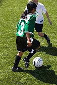 Female footballers (11-13) dribbling, elevated view