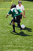 Female footballers (11-13) dribbling