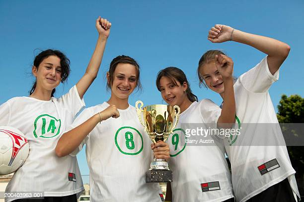 Female footballers (13-15) holding trophy, arms raised in celebration