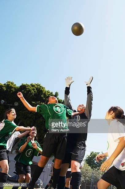 Female footballers (11-13) jumping for ball