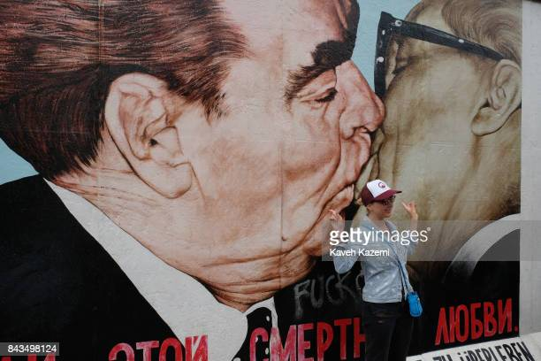 A female foreign tourist poses in front of the mural depicting Leonid Brezhnev and Erich Honecker kissing painted by Dmitri Vrubel in The East Side...