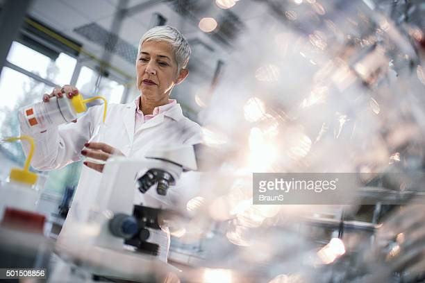 Female forensic scientist working on chemicals in laboratory.