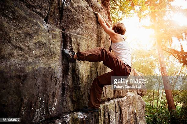 Female free climber climbing rock face