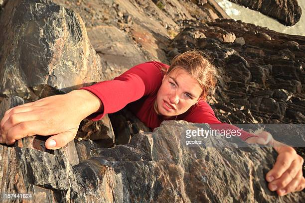 A female free climbing up the side of a mountain