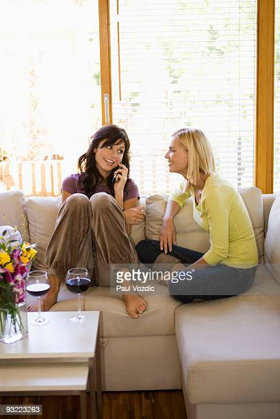 Female friends at home, on phone.