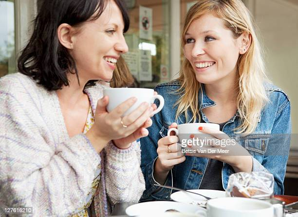 female friends chatting over coffee in cafe.