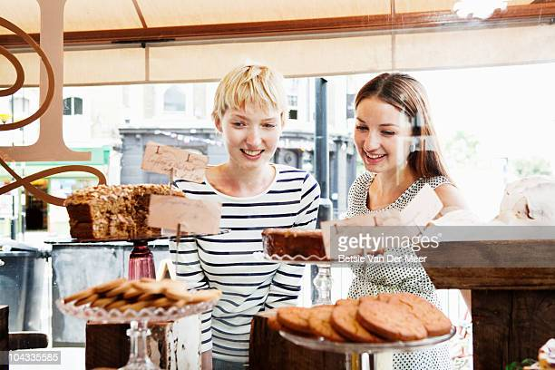 Female friends chosing cakes from cakeshop.