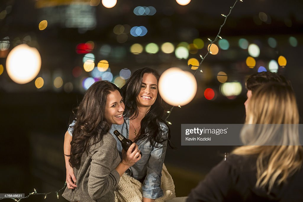 Female friends dancing at rooftop party : Stock Photo
