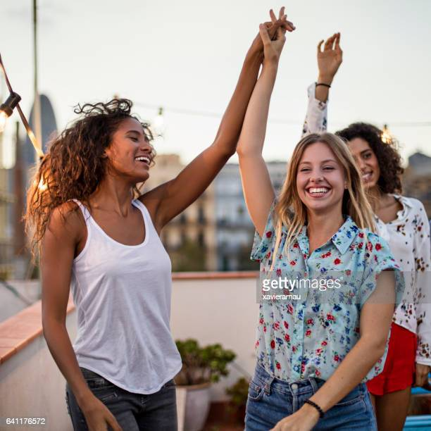 Female friends dancing during party on terrace