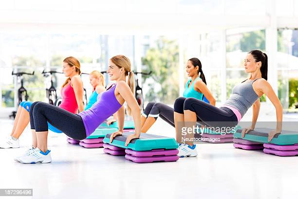 Female Friends Doing Step Aerobics In Gym