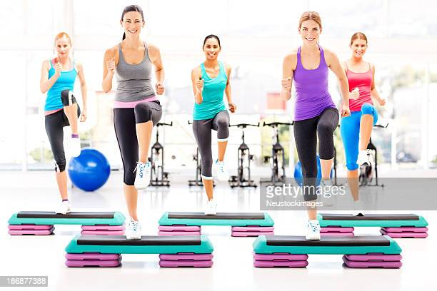 Female Friends Doing Step Exercise In Health Club