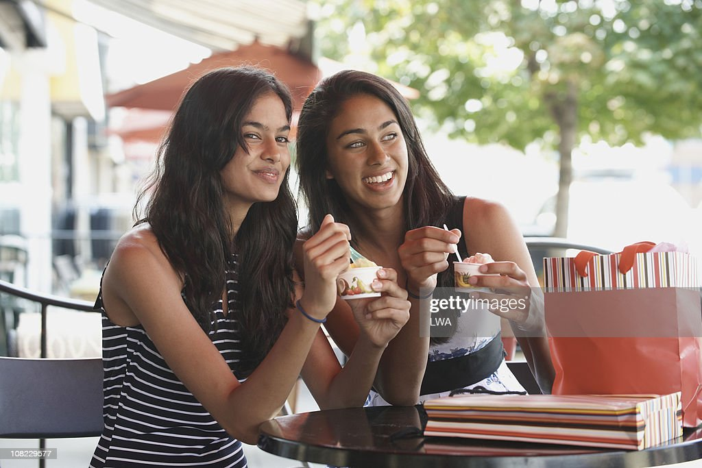 Female Friends Eating Gelato At Cafe : Stock Photo