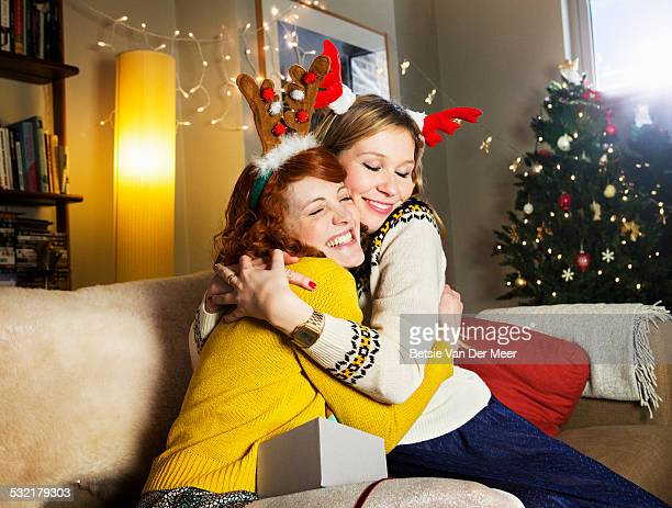 Female friends embrace at Christmas.