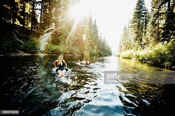 Female friends floating in inner tubes on river