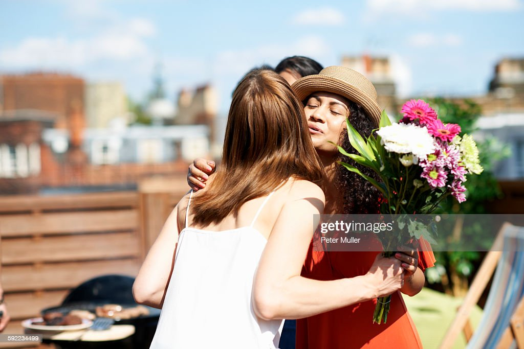 Female friends greeting with flower bouquet at rooftop barbecue : Stock-Foto