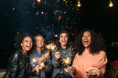 Female friends having party at night outdoors, throwing confetti