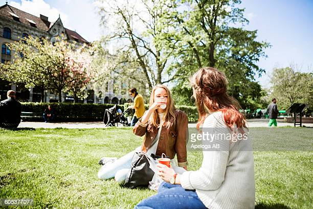 Female friends holding coffee cup while sitting on grassy field at park