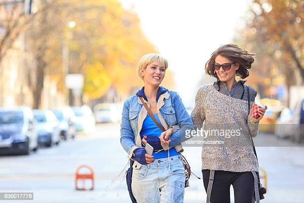 Female friends holding hands and walking on street