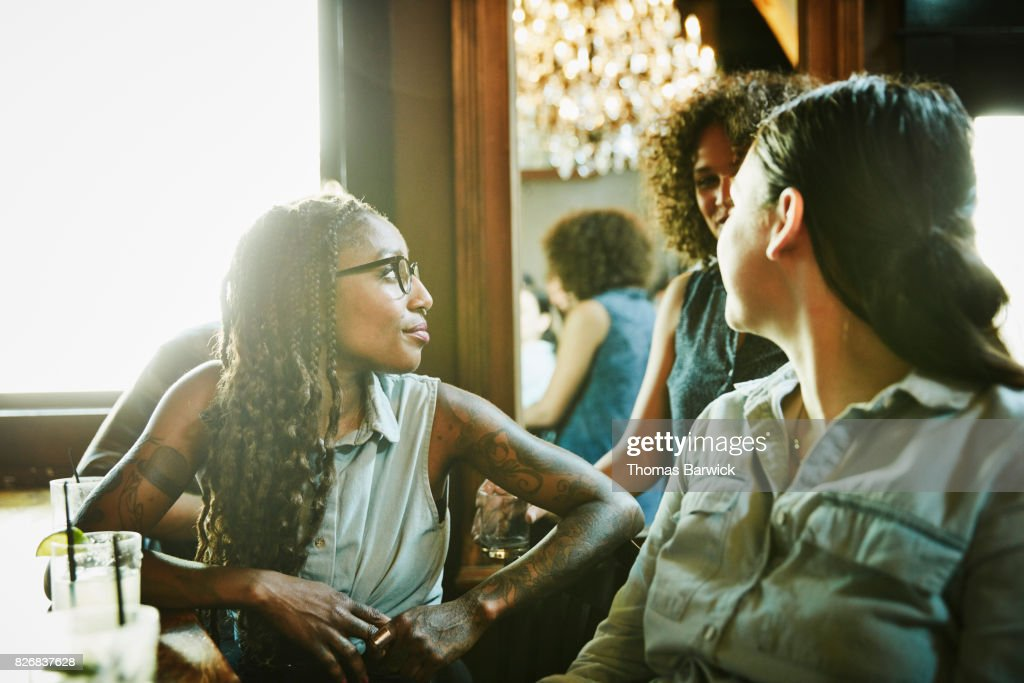 Female friends in discussion while hanging out in bar : Stock Photo
