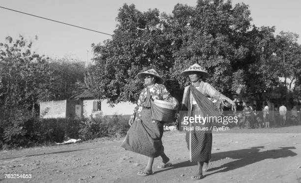 Female Friends In Traditional Clothing Walking On Field