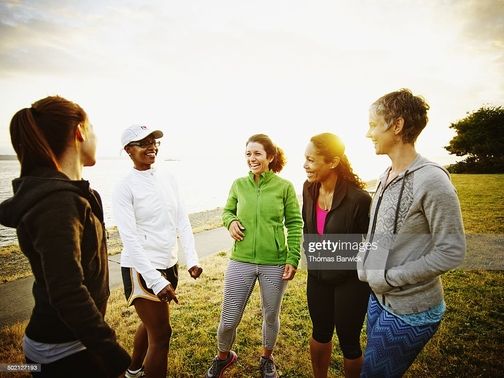 Female friends laughing together after run in park : Stock Photo
