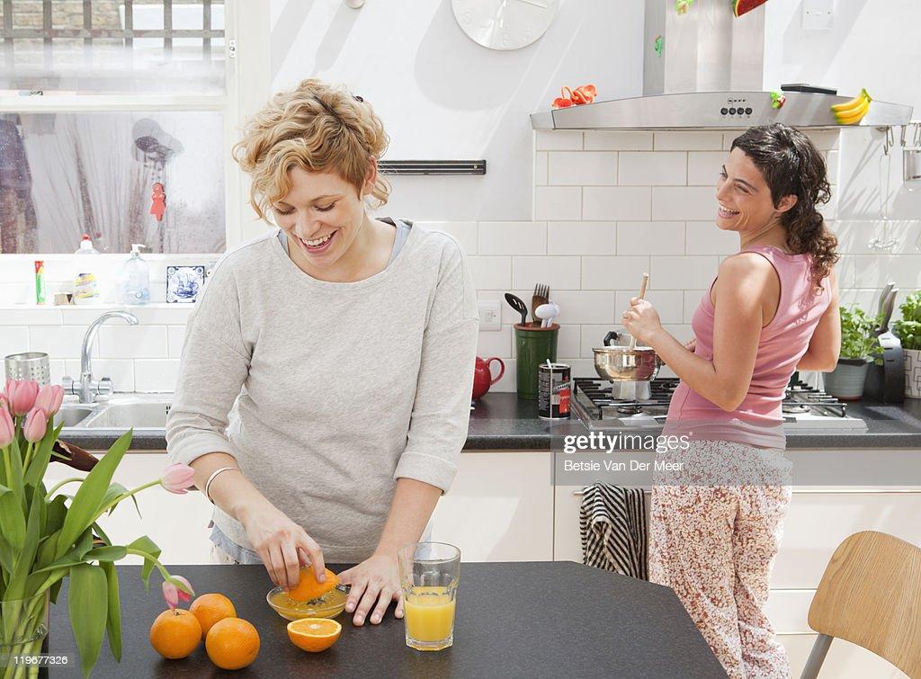Female friends making breakfast in kitchen. : Stock Photo