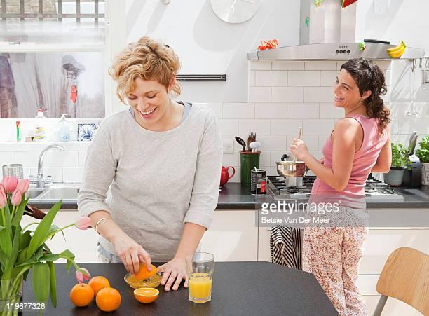 Female friends making breakfast in kitchen.