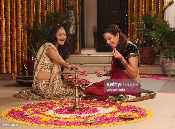Female friends making rangoli on Diwali
