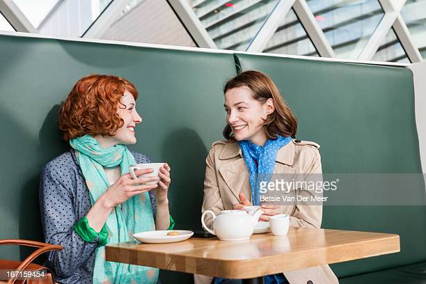 Female friends meeting up in cafe for chat.