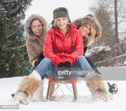 Female Friends on a sled outdoor in the snow flakes