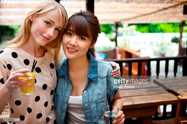 Female friends posing with soft drinks