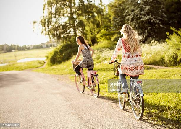 Female friends riding bicycles on country road