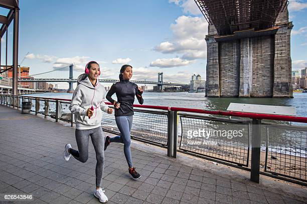 Female friends running along the east river