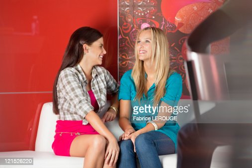 Female friends sitting on a sofa in a cafe : Stock Photo