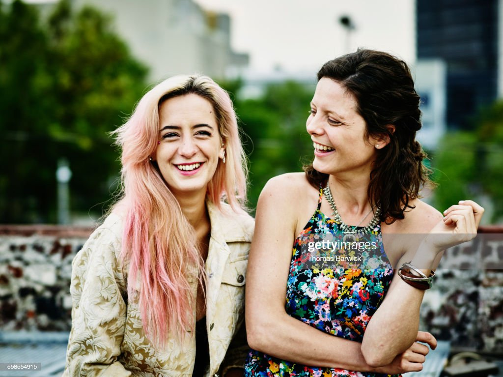 Female friends sitting together on rooftop : Stock Photo