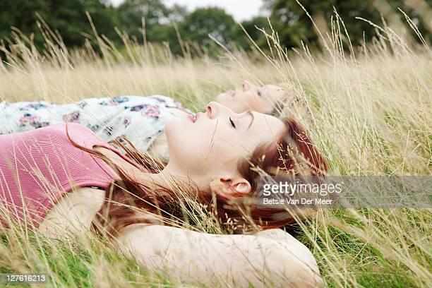 female friends sleeping in grass in park.