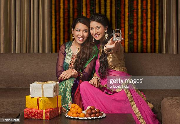 Female friends taking a picture of themselves on Diwali